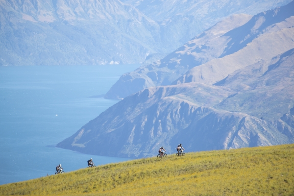 Competitors mountain biking high above Lake Wanaka in the 2019 Red Bull Defiance